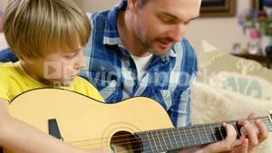 Smiling father and son playing the guitar