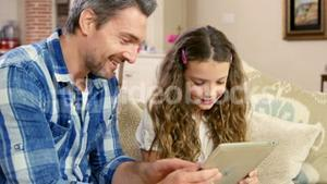 Smiling father and daughter using tablet
