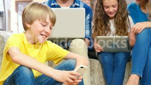 Family using devices on the sofa