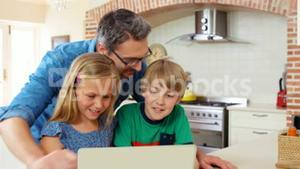 Smiling father and kids using laptop