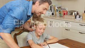 Lovely father helping his son with homework