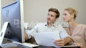 Business people looking at files and working on computer