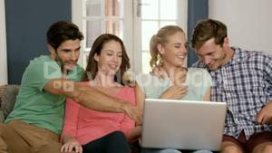 Happy couples using laptop together