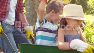 Father holding his children in a wheelbarrow