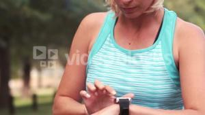 Fit woman setting heart rate watch