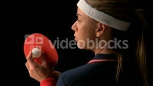 Female ping pong player holding ball and racket