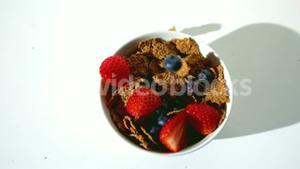 Strawberries and blueberries falling in a wheat cereals bowl