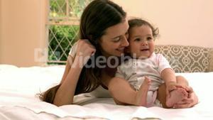 Mother with cute baby sitting on bed