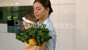 Mother carrying baby and grocery bag
