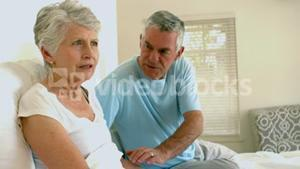 Worried senior couple on bed