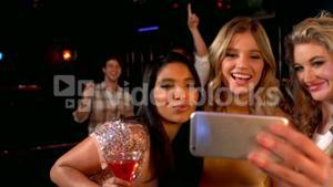 happy friends taking selfie at the night club
