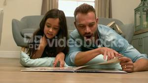 happy father and daughter reading book