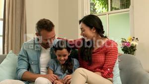 Happy parents talking with their daughter on the sofa