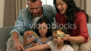 Happy family eating pizza on the sofa