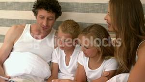 Cute family reading a book on their bed