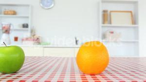 Green apple and orange on a tablecloth