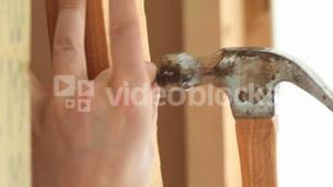 Masculine hands nailing a wooden board