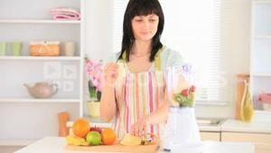 Darkhaired woman preparing a smoothie
