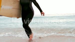 Senior woman running with surfboard