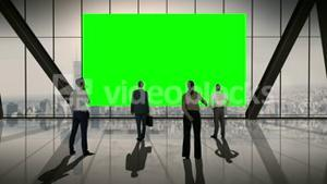 Business people standing in front of a screen