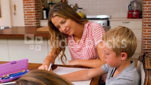 Mother helping her children to do their homework
