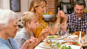 Cute family praying before eating dinner