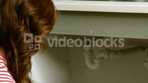 Woman kneeing in front of sink