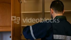 Man looking in cupboard for pest control