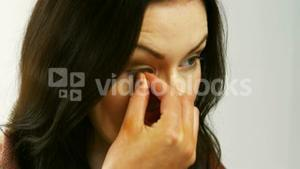 Woman removing her contact lenses