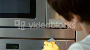 Woman cleaning the microwave