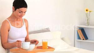 Brunette woman eating breakfast on a bed