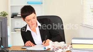 Upset brunette woman working with a calculator