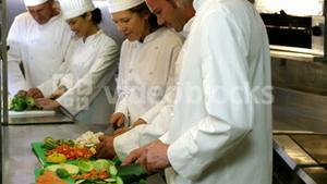 Chef chopping vegetables on green board