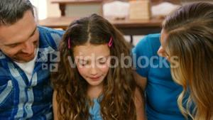 Parents talking with their daughter on couch