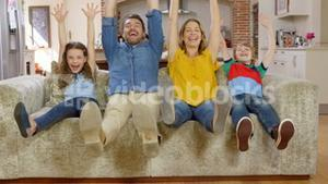 Family waving at camera on couch