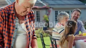 Family having a barbecue together in garden