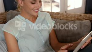 Cute blonde using tablet on couch