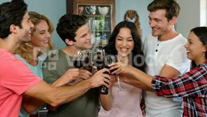 Happy friends cheering with wine glasses