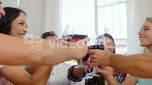 Happy friends cheering with red wine