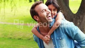 Happy father piggybacking daughter