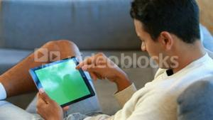Man using a tablet sitting on the couch