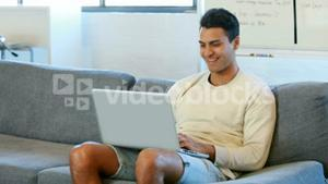 Man using a laptop sitting on the couch