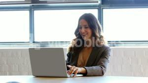 Businesswoman using her laptop at work