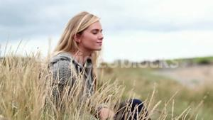 Blonde woman relaxing in the dunes in cinemagraph