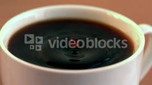 Drop falling into cup of coffee in cinemagraph