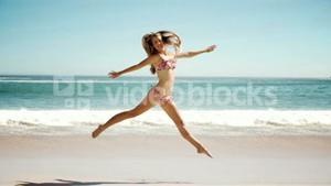 Happy young woman jumping on beach in cinemagraph
