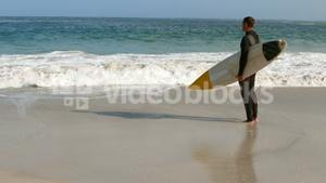 Man in wet suit holding surfboard