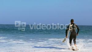 Man in wet suit running into water