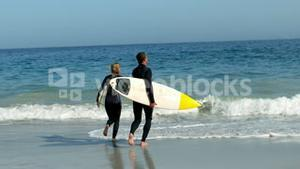 Couple running into water with surfboard