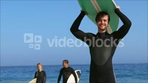 Friends in wet suit holding surfboard